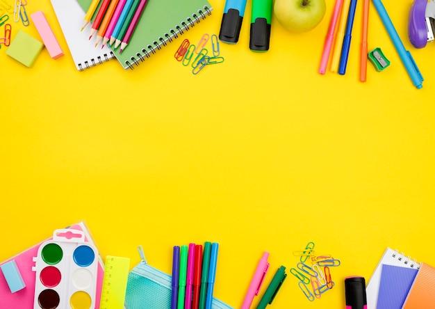 Postura plana de itens essenciais da escola com lápis e aquarela
