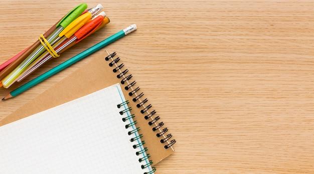 Postura plana de itens essenciais da escola com lápis e cadernos