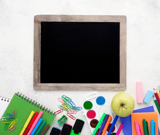 Postura plana de itens essenciais da escola com lápis e quadro-negro