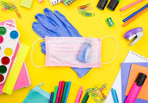 Postura plana de itens essenciais da escola com luvas e lápis