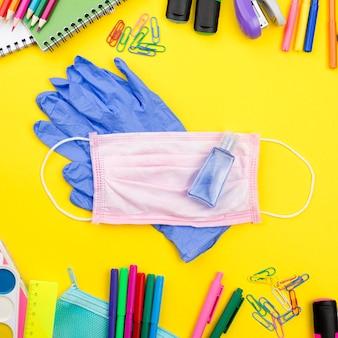 Postura plana de itens essenciais da escola com luvas e máscara médica