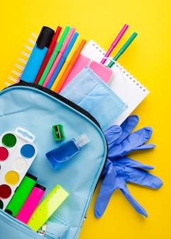 Postura plana de itens essenciais da escola com luvas e mochila