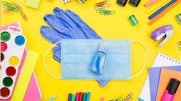 Postura plana de itens essenciais da escola com máscara médica e luvas