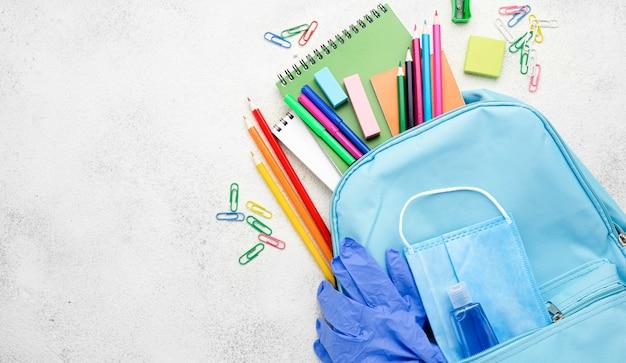 Postura plana de itens essenciais da escola com mochila e cópia de espaço