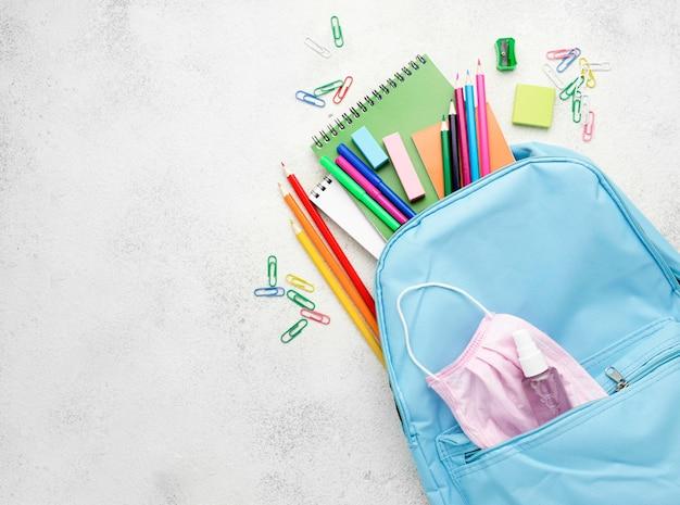 Postura plana de itens essenciais da escola com mochila