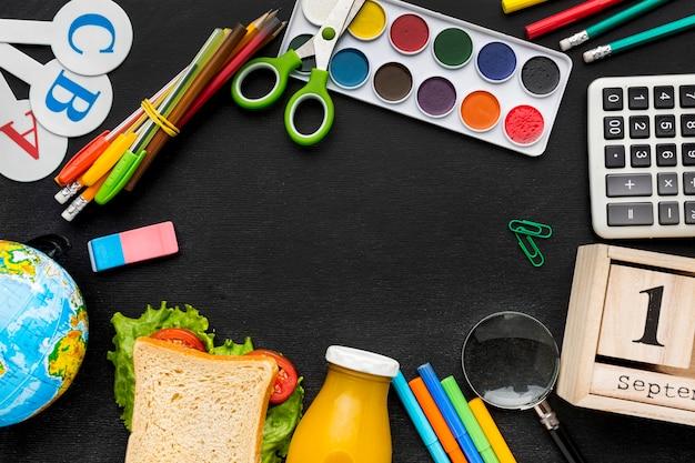Postura plana de itens essenciais da escola com sanduíche e aquarela