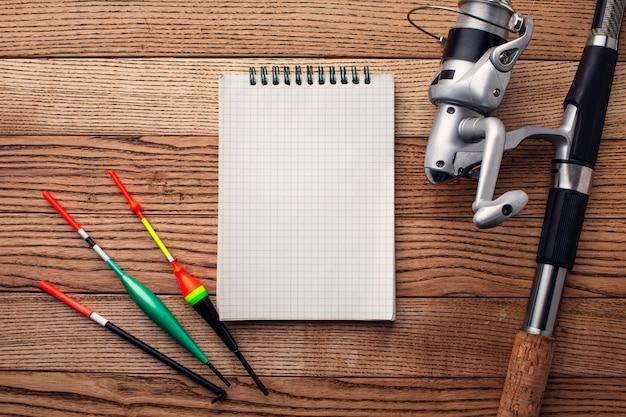 Postura plana de itens essenciais de pesca com notebook