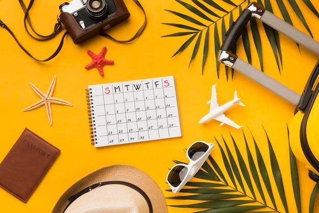 Postura plana de itens essenciais de viagem com calendário e óculos de sol