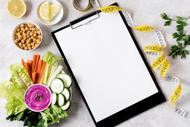 Postura plana de legumes com grão de bico e caderno