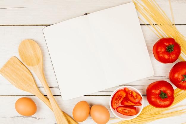 Postura plana de livro e ingredientes alimentares com espaço de cópia