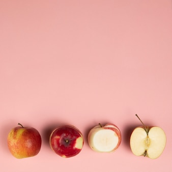 Postura plana de maçã no fundo rosa com espaço de cópia