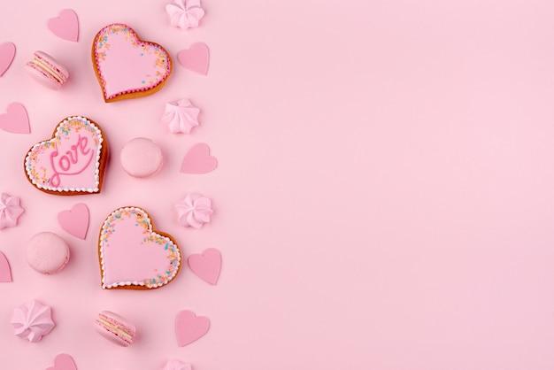 Postura plana de macarons e biscoitos em forma de coração para dia dos namorados