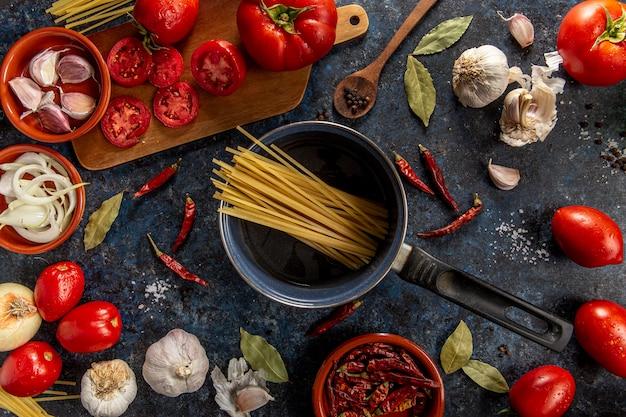 Postura plana de macarrão na panela com tomates e legumes