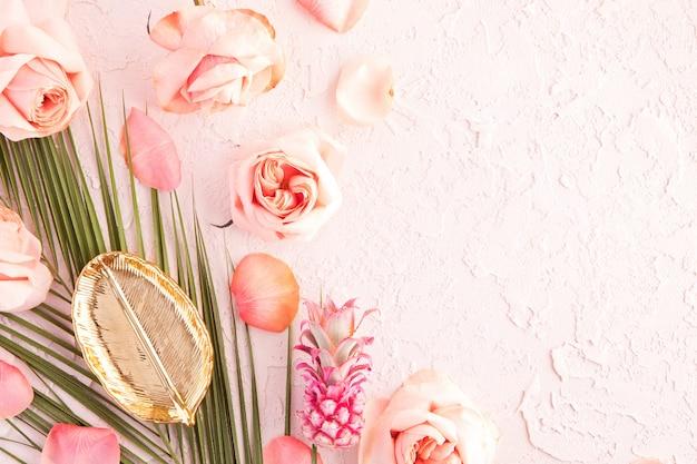 Postura plana de maquete de espaço de trabalho tropical com palm monstera folhas, flores cor de rosa, abacaxi e pétalas em pastel