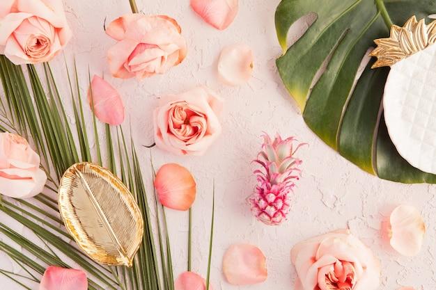 Postura plana de maquete de espaço de trabalho tropical com placa de folha, folhas de palm monstera, flores cor de rosa, abacaxi e pétalas em pastel