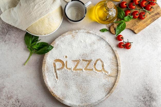 Postura plana de massa de pizza com placa de madeira e palavra escrita em farinha
