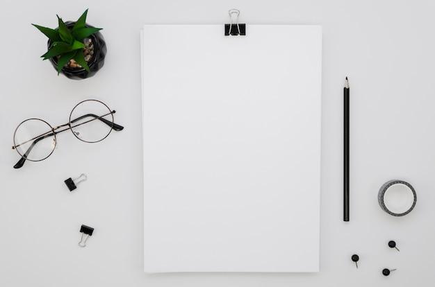 Postura plana de material de escritório com óculos e planta