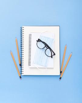 Postura plana de material escolar com óculos e máscara facial