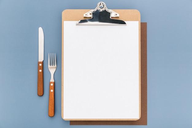 Postura plana de menu em branco com garfo e faca