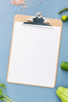 Postura plana de menu em branco com legumes
