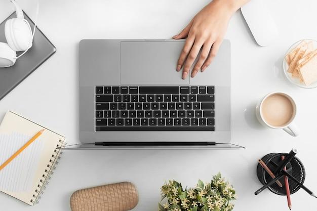 Postura plana de mesa com mão e computador portátil