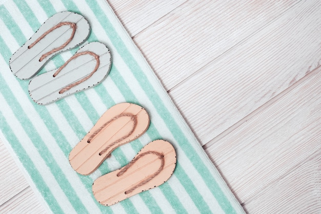 Postura plana de miniatura composta de área de lounge de praia com sapatos de verão - chinelos de dois pares, toalha de terry