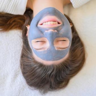 Postura plana de mulher em casa com máscara facial