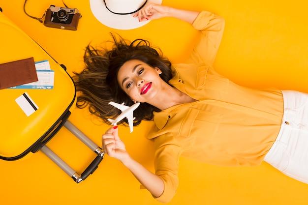 Postura plana de mulher rodeada por elementos essenciais de viagem