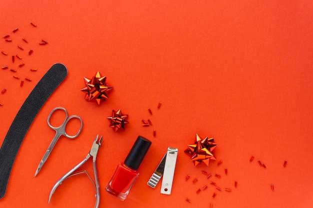 Postura plana de natal de acessórios de manicure e esmaltes com decorações do feriado em um fundo vermelho. espaço para texto.