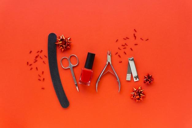 Postura plana de natal de acessórios de manicure e esmaltes com decorações do feriado em um fundo vermelho.