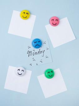 Postura plana de notas adesivas com rosto triste para segunda-feira azul e rostos sorridentes