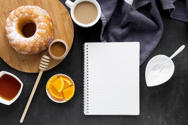 Postura plana de notebook com donuts e café