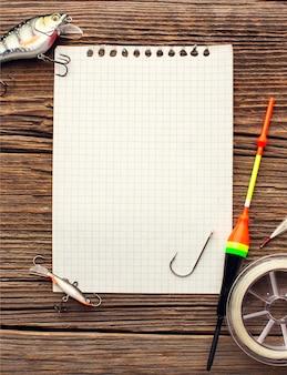 Postura plana de notebook com equipamentos e itens essenciais de pesca