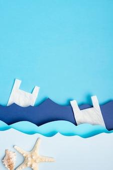 Postura plana de ondas do mar de papel com sacos de plástico e estrela do mar