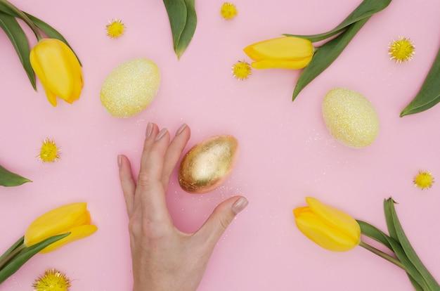 Postura plana de ouro ovo de páscoa com dentes de leão e tulipas