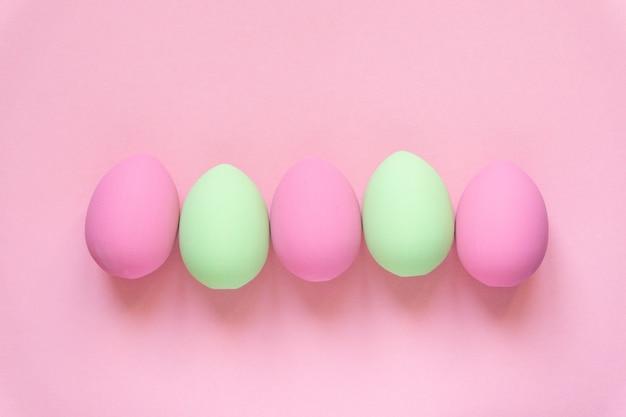 Postura plana de ovos de páscoa de cor rosa e verde