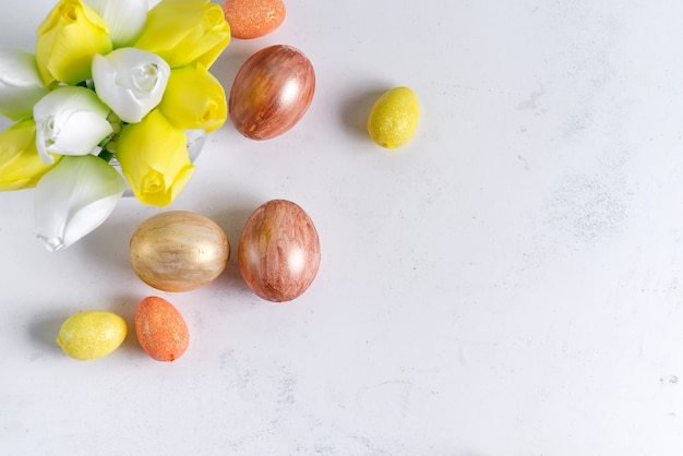 Postura plana de ovos de páscoa de ouro com tulipas em fundo de pedra mármore. fundo de páscoa ou conceito de páscoa.
