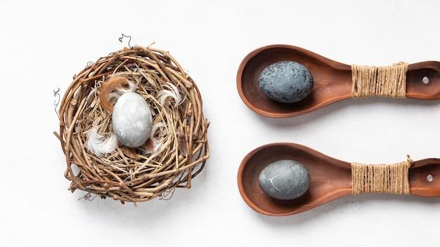 Postura plana de ovos de páscoa em ninho de pássaro e colheres de madeira
