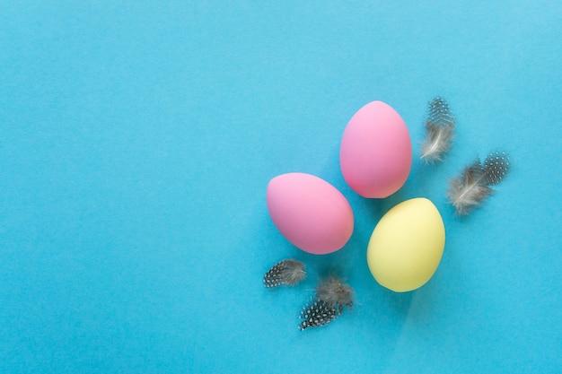 Postura plana de ovos de páscoa pintados de amarelo e rosa com penas em fundo azul, copie o espaço