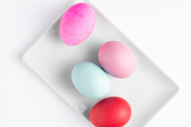 Postura plana de ovos de páscoa pintados no prato