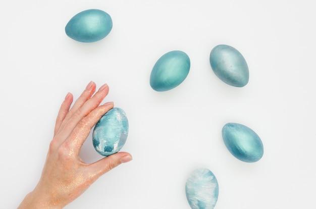 Postura plana de ovos tingidos para a páscoa com a mão