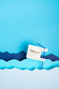 Postura plana de palha de plástico com ajuda nas ondas do mar de papel