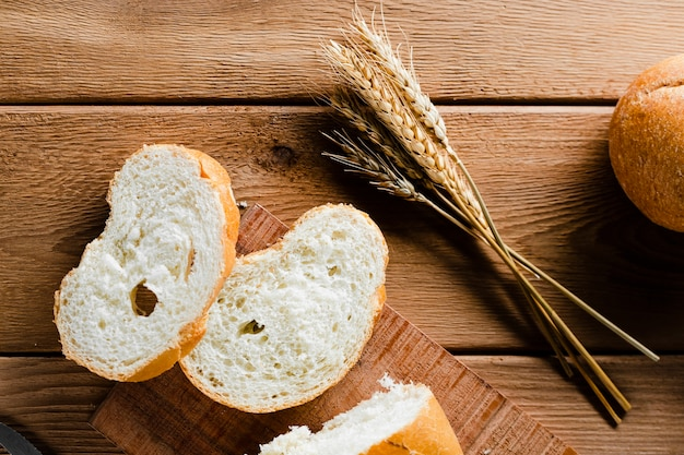 Postura plana de pão fatiado na mesa de madeira