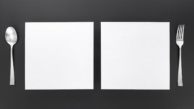 Postura plana de papéis de menu em branco com garfo e colher