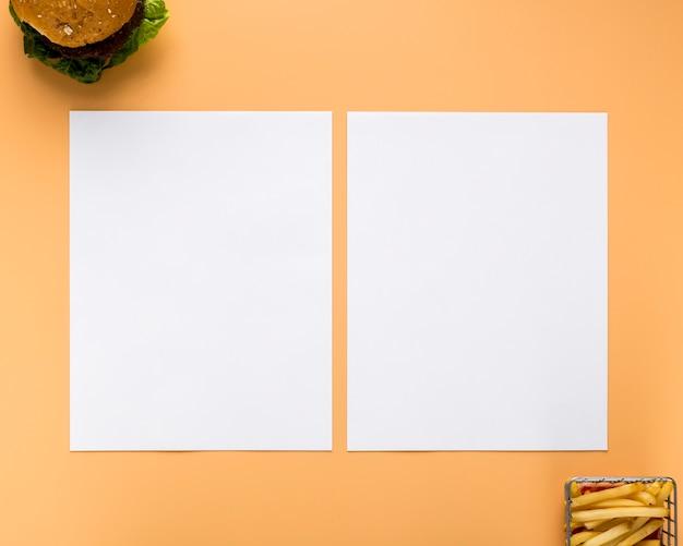 Postura plana de papéis de menu em branco com hambúrguer e batatas fritas