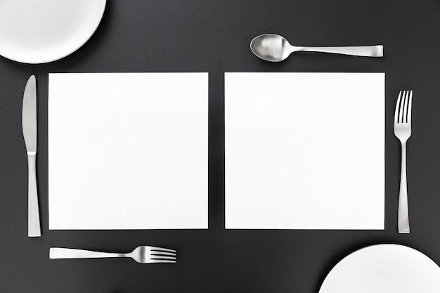 Postura plana de papéis de menu em branco com talheres e pratos