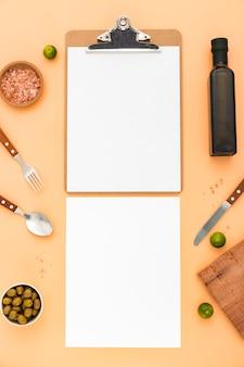 Postura plana de papel de menu em branco com azeitonas e talheres