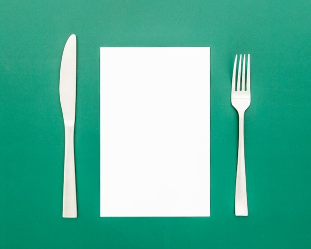 Postura plana de papel de menu em branco com garfo e faca