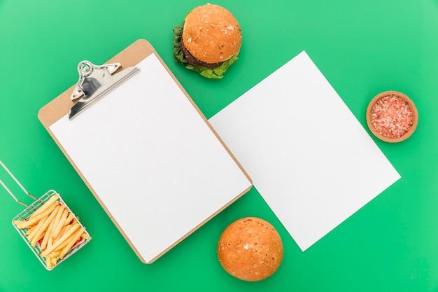 Postura plana de papel de menu em branco com hambúrgueres e batatas fritas