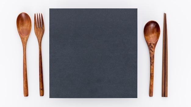 Postura plana de papel de menu em branco com talheres de madeira